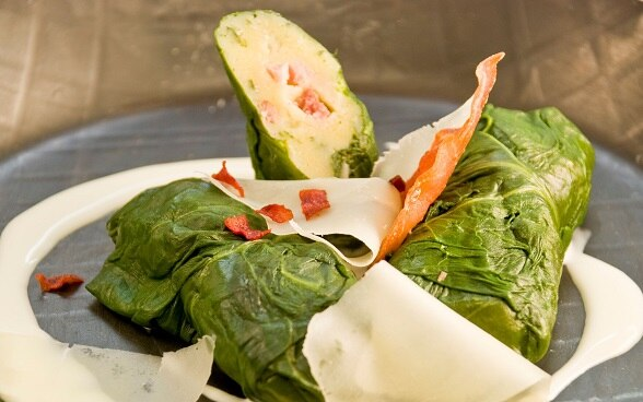 Capuns, chard leaves stuffed with spätzli dough and pieces of dried meat