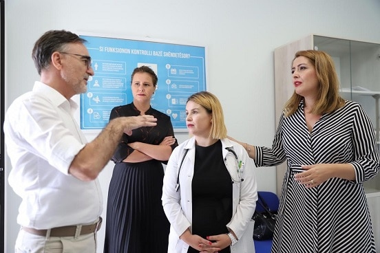Director of 'Health for All' project Besim Nuri discussing with Albania's Minister of Health Ogerta Manastirliu at the health centre in Sauk, Tirana