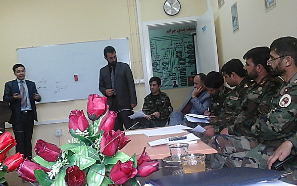 A human rights defender briefs members of the Afghan army who are dressed in military uniform.