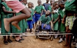 Group of Nigerian schoolchildren skipping rope while a smiling child in a wheelchair looks on.