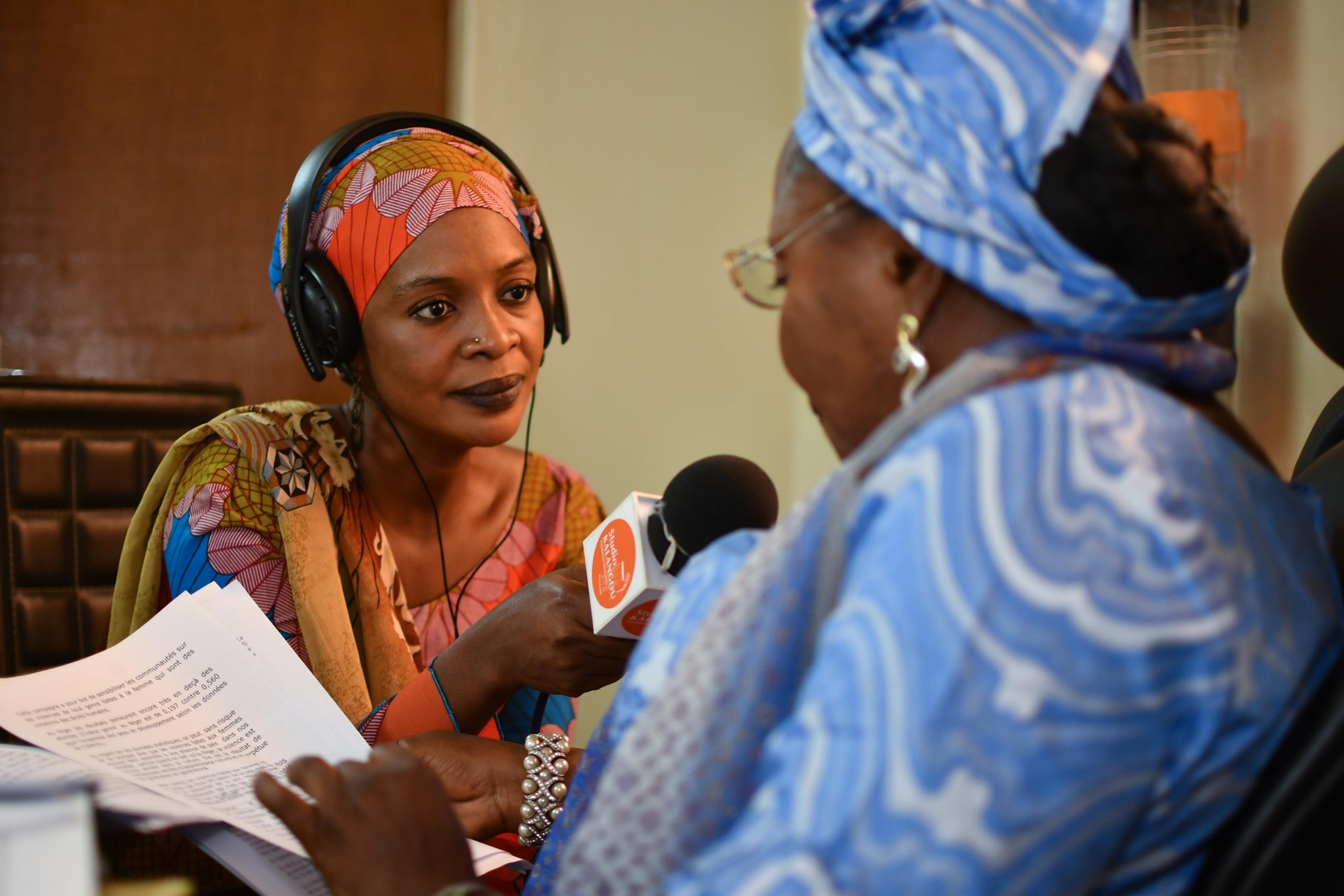 An African woman holds a microphone as she interviews another woman in a radio studio.