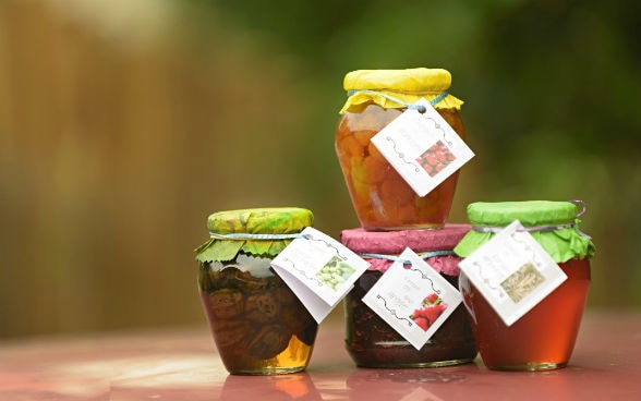 Four jars containing different kinds of preserves.