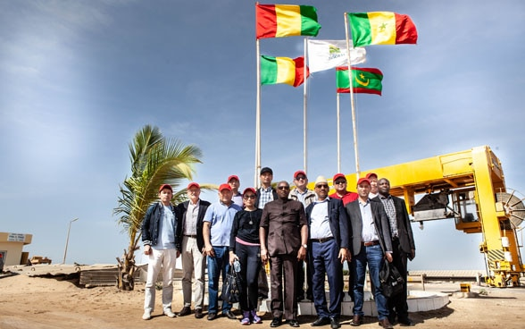 High-level government representatives from Central Asia and West Africa standing in front of a large water pipe.