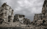 People walk through the ruins of the Syrian town of Idlib, which was hit by air raids.
