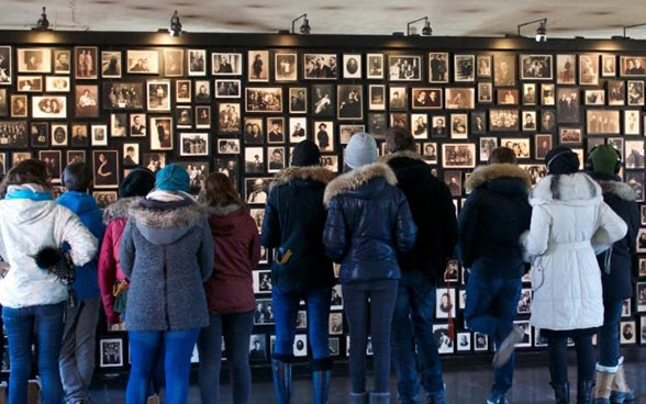 A group of Swiss youngsters looking at a wall featuring portraits of Holocaust victims.