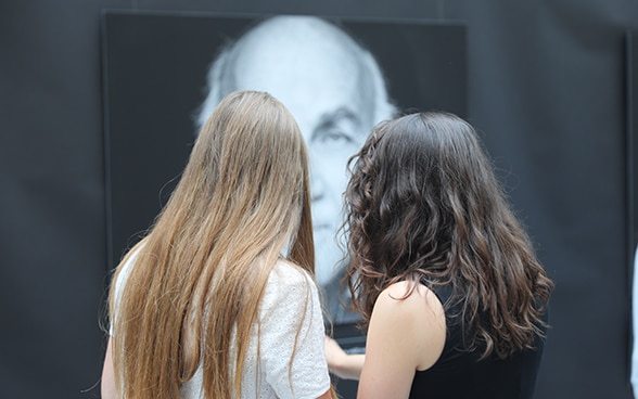 Two school students looking at a poster in the exhibition.