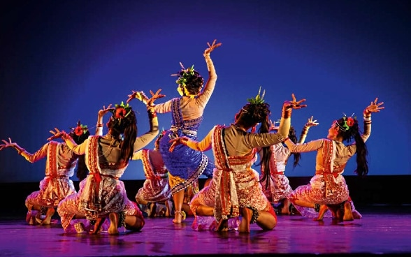Seven colourful dancers on one stage.