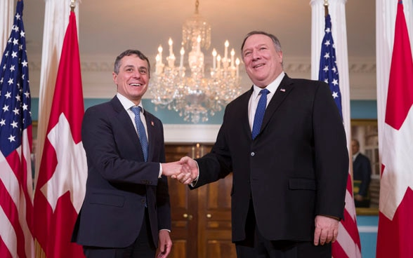 Federal Councillor Ignazio Cassis shakes hands with US Secretary of State Mike Pompeo in Washington. The flags of Switzerland and the USA can be seen in the background.