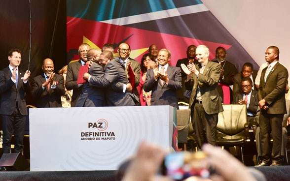 Representatives of the parties to the conflict embrace each other after the signing of the peace agreement.