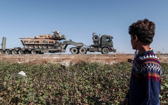 A worker in a cotton field in Sanliurfa region observes the passage of a Turkish military vehicle heading towards north-eastern Syria