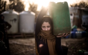 A young woman carries a green water canister on her shoulder.