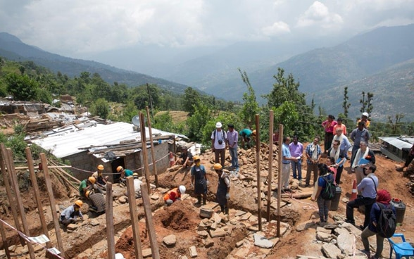 Alt: A construction site where Nepalese workers are rebuilding the walls of a house on a wooded slope.