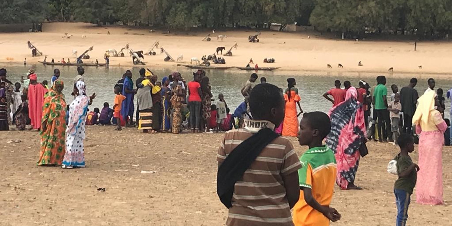 People wearing brightly coloured clothing standing on the bank of the Senegal River which separates Senegal and Mauritania.