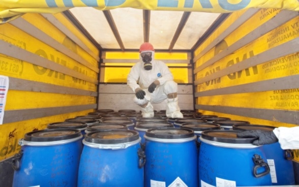 Man in protective clothing on a truck with containers of pesticides.