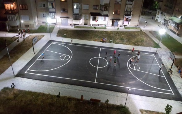 : A group of young people playing on a floodlit basketball court.