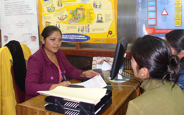 Two women engaged in a discussion with a psychologist at a counselling centre