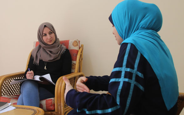 A therapist counselling a patient in a consultation room.