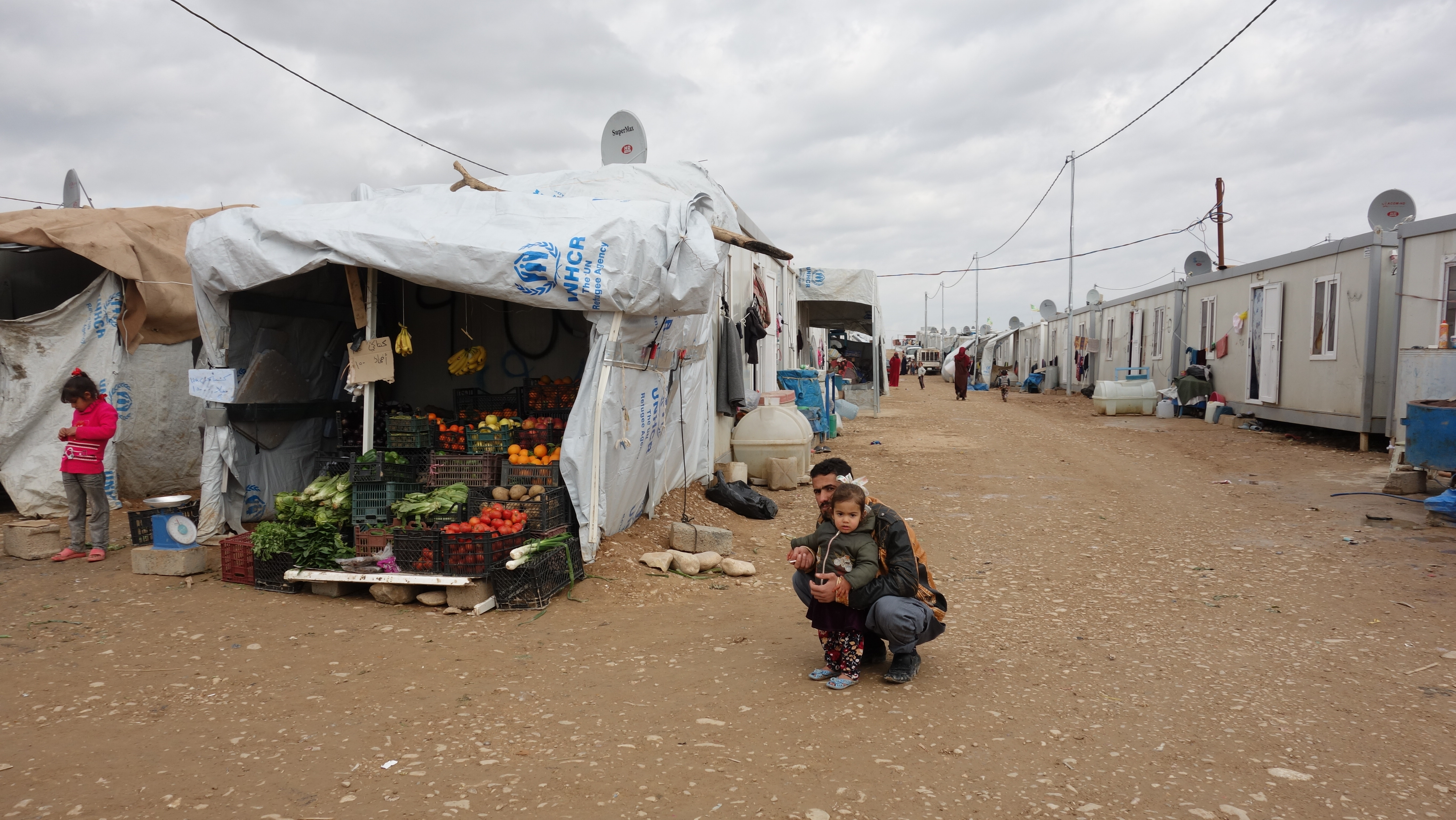 A female child with her dad beside a tent of the UNHCR with fruits and vegetables.