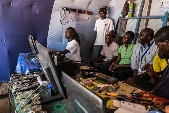 a man repairing a computer in his workshop, watched by six visitors.