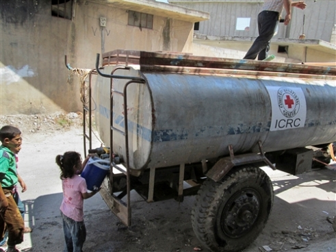 A little girl – one of millions of people displaced inside Syria – fetches water from an ICRC tanker in Talbiseh on the outskirts of Homs.