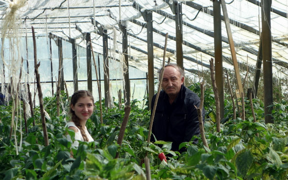 The photo shows Medea and her instructor among rows of peppers in the college greenhouse.