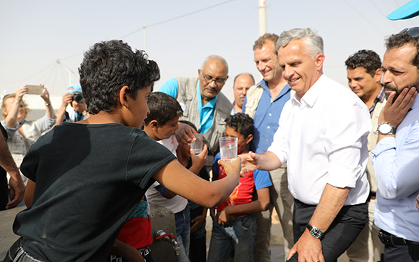 A young Syrian refugee hands a glass of water to Federal Councillor Didier Burkhalter