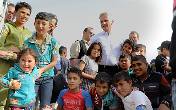 A crowd of refugee children standing next to the head of the FDFA