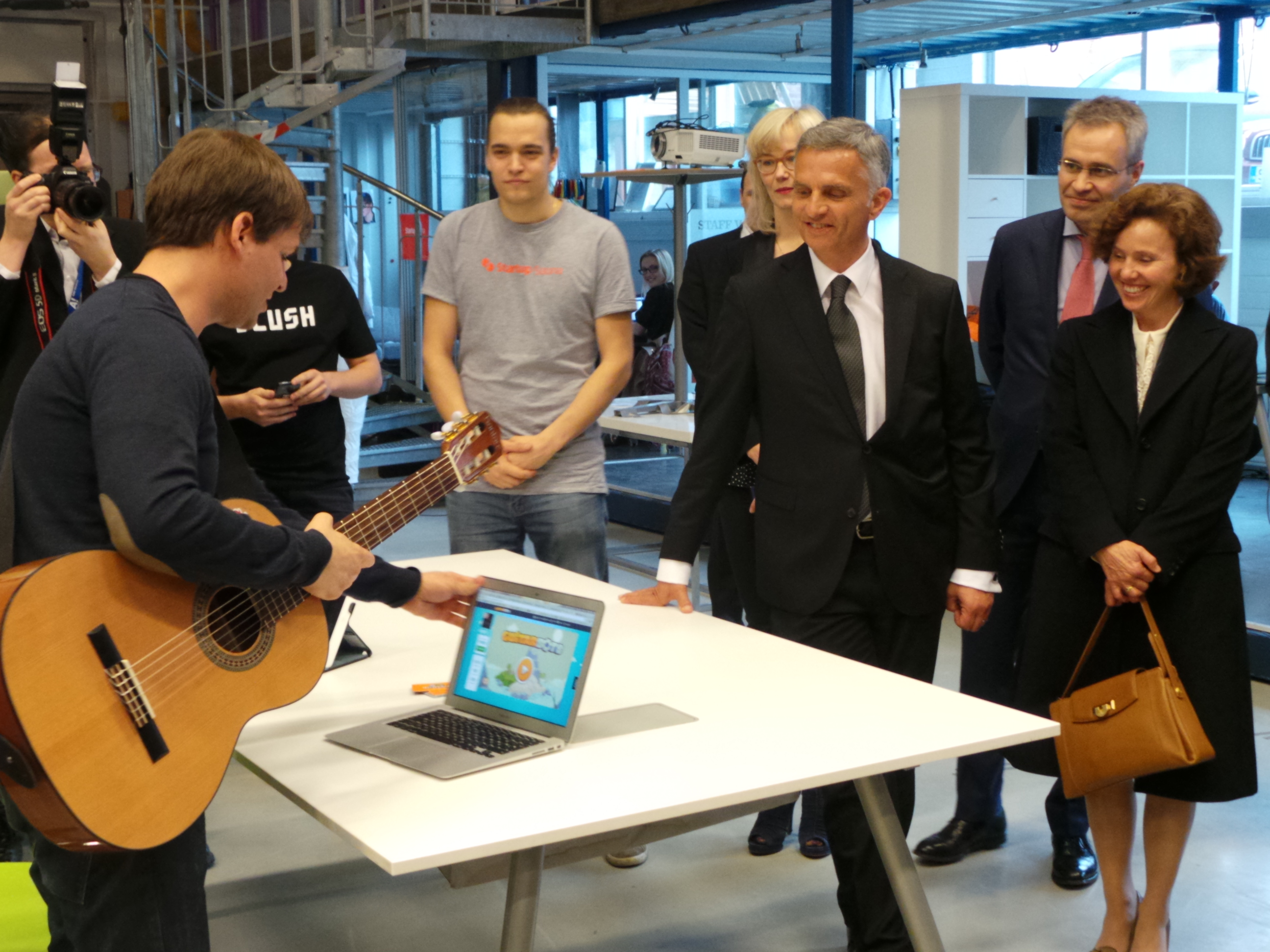 A Swiss explains a computer program on learning to play the guitar to President Didier Burkhalter and his wife.