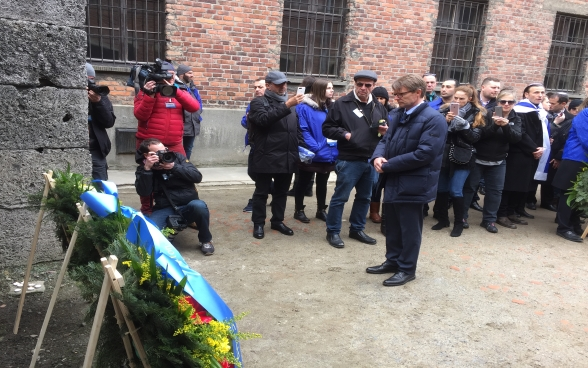 Benno Bättig, Chair of the International Holocaust Remembrance Alliance (IHRA), lays a wreath at the Death Wall in Auschwitz during the March of the Living.