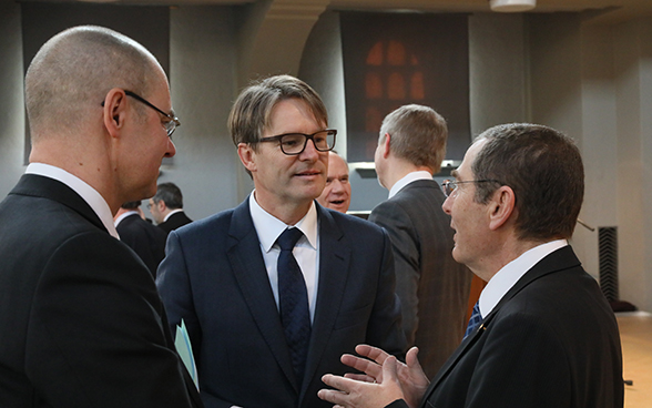 Benno Bättig, FDFA secretary-general and chairman-designate of the IHRA (centre), speaking with Israel's ambassador to Switzerland, Jacob Keidar (right), and François Wisard, head of the FDFA History Unit.