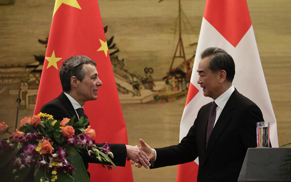 Swiss Foreign Minister Ignazio Cassis shakes hands with Chinese State Councilor and Foreign Minister Wang Yi after their joint press conference in Beijing, April 3, 2018.
