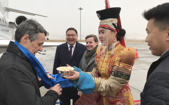 A woman in traditional dress presents Federal Councillor Cassis with a small bowl as he leaves the plane.