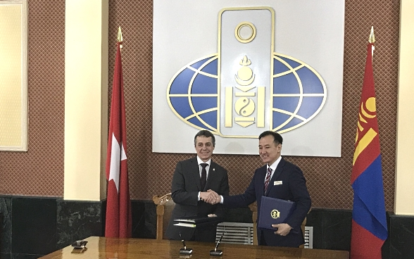Mr Cassis and his Mongolian counterpart Damdin Tsogtbaatar shaking hands at an official meeting.